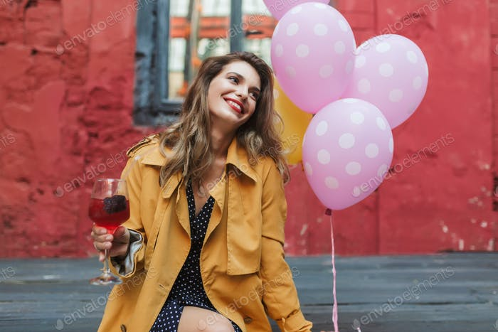 Young attractive smiling woman in orange trench coat holding coc