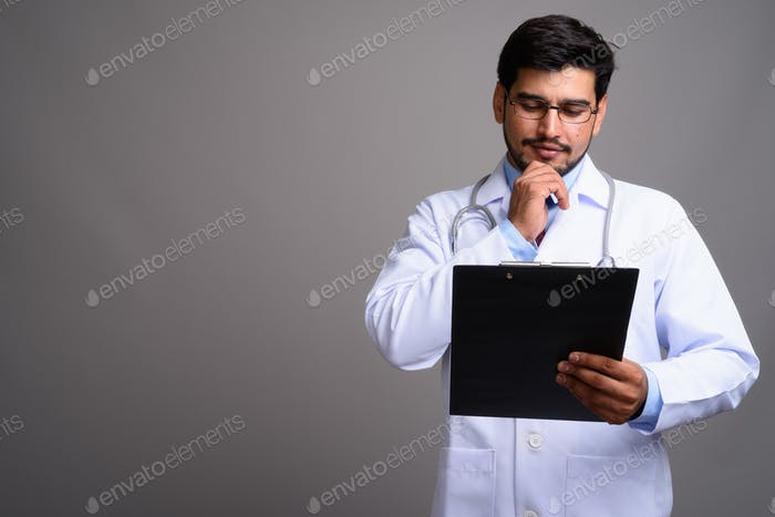 Young handsome bearded Persian man doctor against gray backgroun