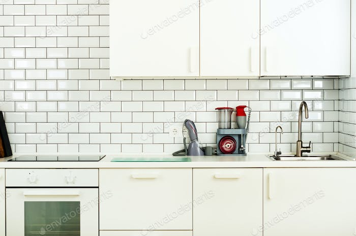 White minimalistic kitchen interior and design. Tile wall background. Household appliances - blender