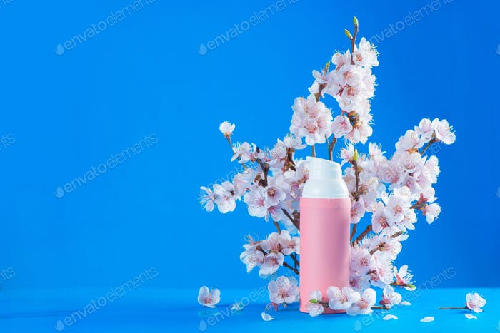 Cherry blossom cosmetics header. Pink creme tube with spring flowers on a sky blue background with