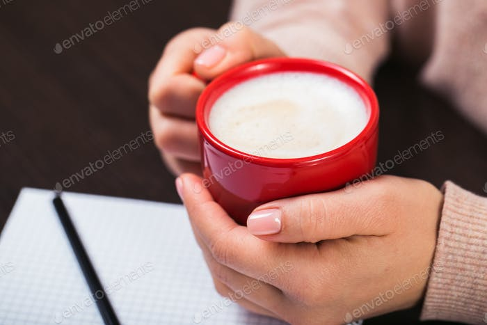 Woman holding a red cup of coffee. Gift box with red ribbon and white notebook
