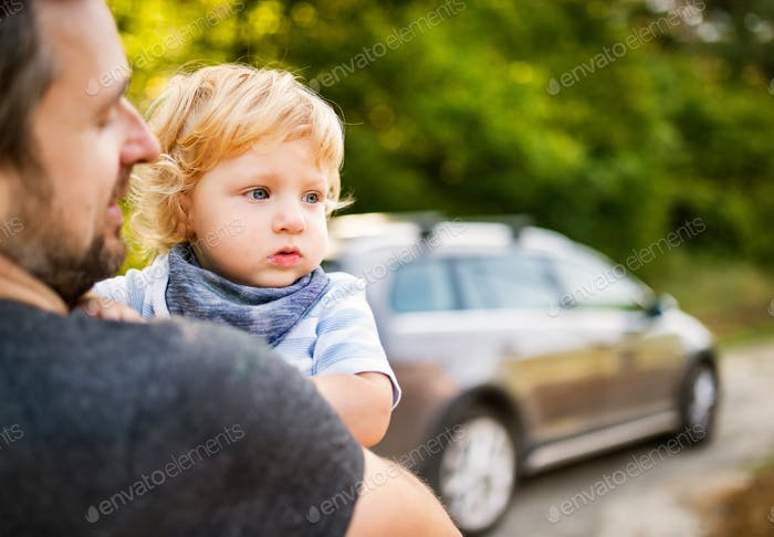 Young father with his little son going into the car.