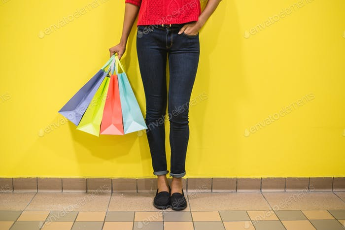 Woman legs with colourful shopping bags in a colourful wall