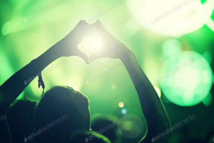 Silhouette of hands on a concert doing the love sign in front of bright stage lights