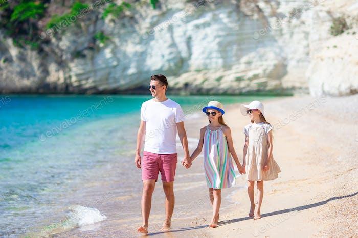 Glückliche schöne Familie von Papa und Kinder am weißen Strand