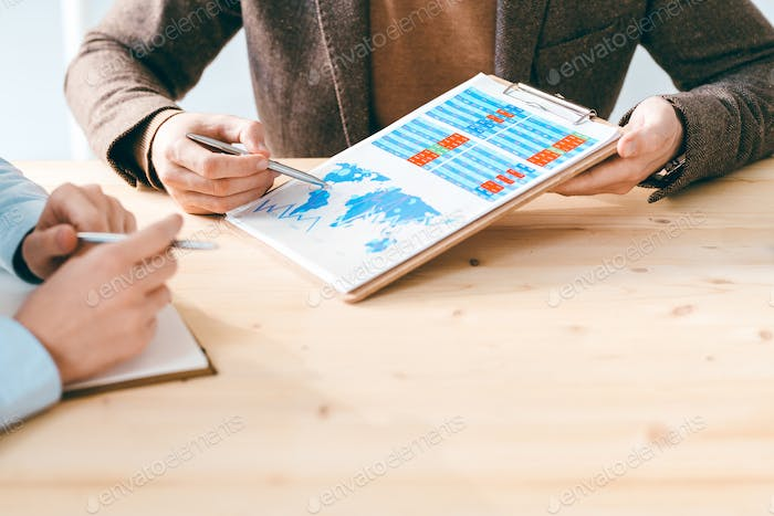 Contemporary businessman showing colleague document with financial chart