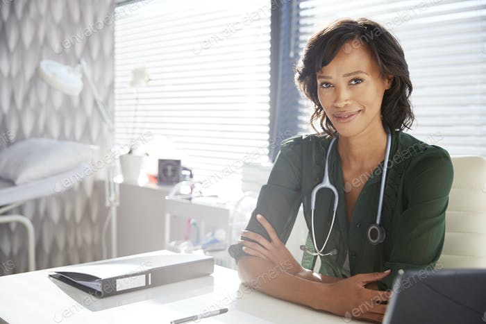 Portrait Of Smiling Female Doctor With Stethoscope Sitting Behind Desk In Office