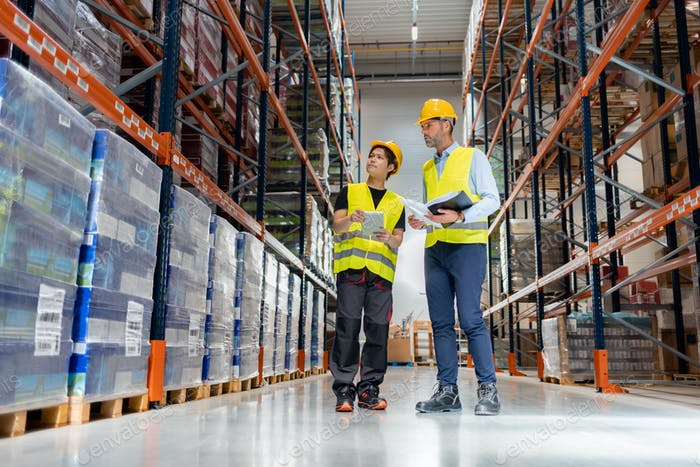 Warehouseman and manager looking at packages in large warehouse