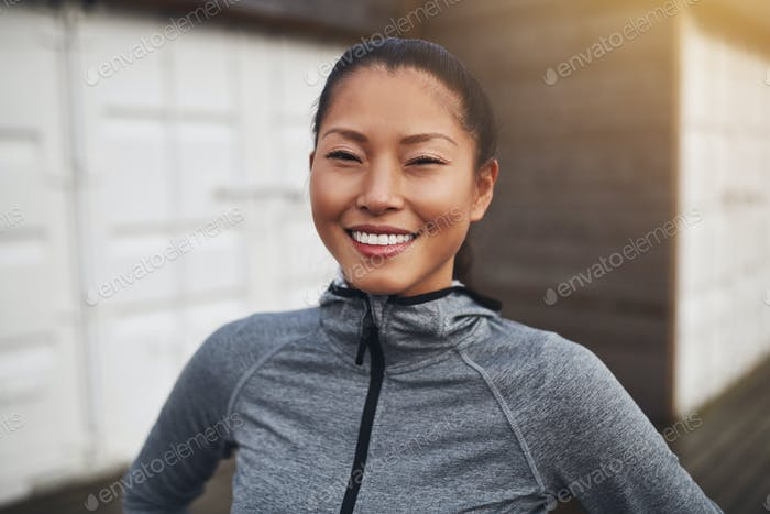 Smiling young Asian woman in sportswear out for a run