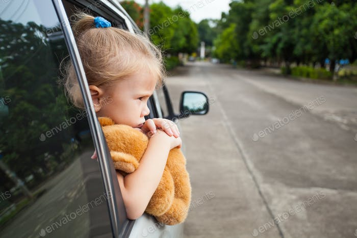 sad little girl sitting near the window in the car