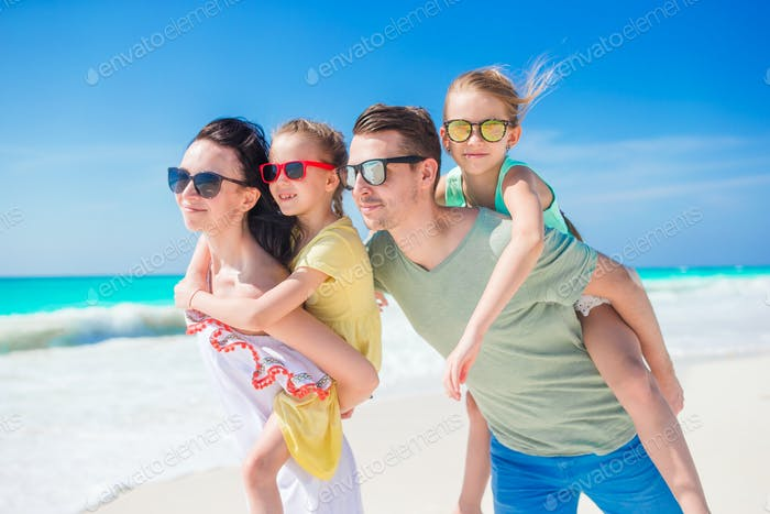 Happy beautiful family of four on beach on vacation