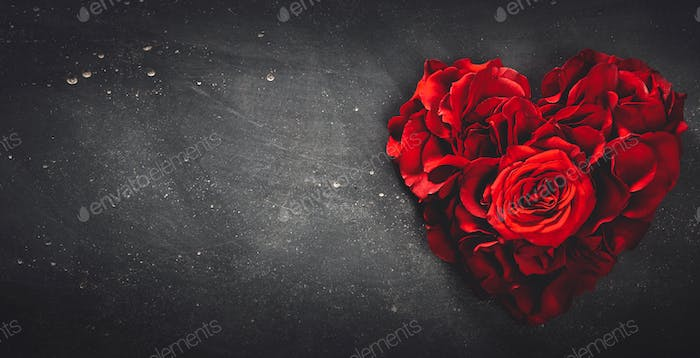 Red roses in heart shape on grey stone background