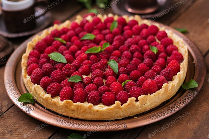 Tart with raspberries and whipped cream decorated with mint leaves on a wooden background.