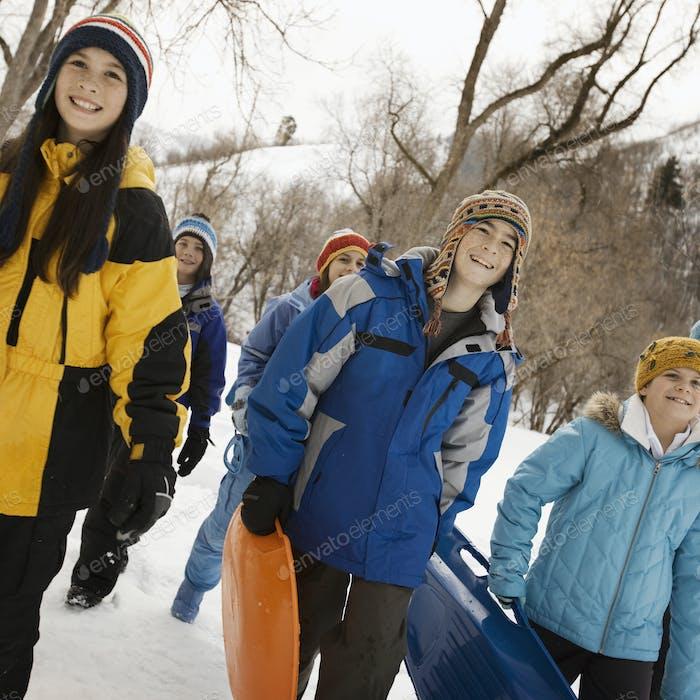 Eine Gruppe von Kindern, Jungen und Mädchen, die Schlitten über den Schnee tragen.