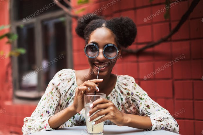 Pretty african girl in blouse and sunglasses joyfully looking as