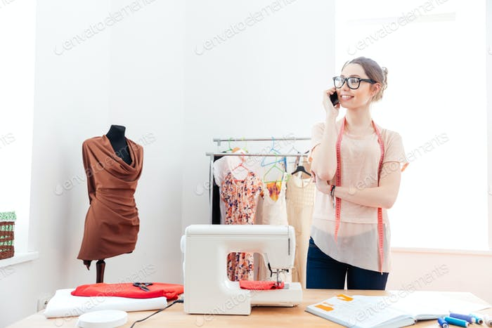 Woman seamstress standing and talking on cell phone in workshop
