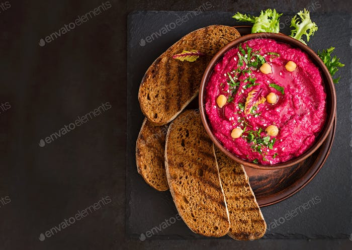 Roasted Beet Hummus with toast in a ceramic bowl on a dark background. Top view