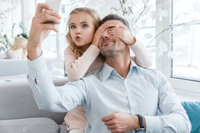 daughter covering eyes of father and grimacing while they taking selfie