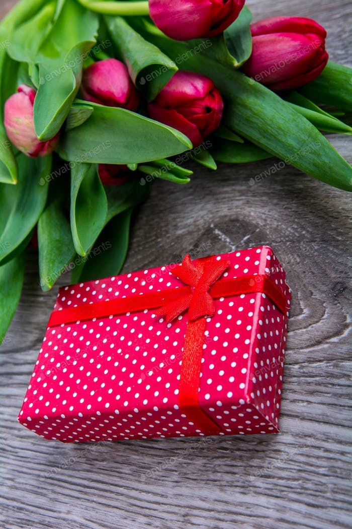 Red tulips and gift on a wooden table