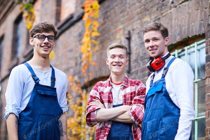 Fröhliche junge Arbeiter in Uniformen im freien