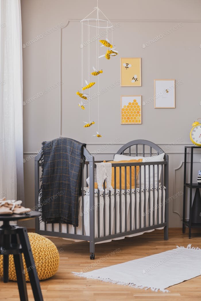 Installation with yellow and black bees above grey wooden crib w