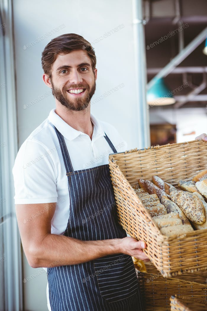 Portrait of happy worker holding basket of bread at the bakery