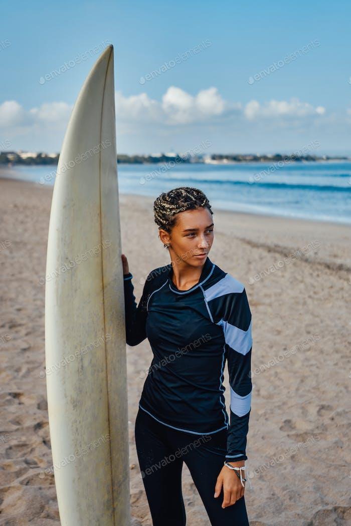 Woman with dreadlocks and surfboad on beach