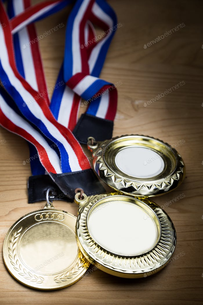 Three sporting event gold medal with red and blue ribbon