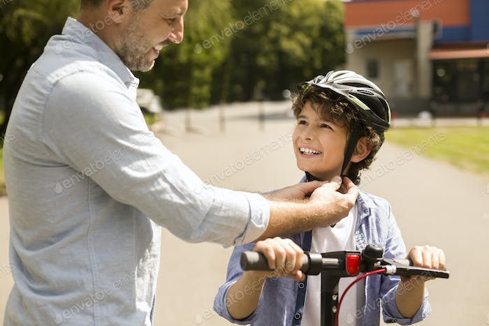 Adult man putting protective helmet on curly boy