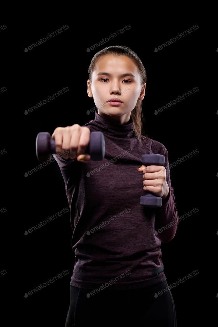 Young active female with dumbbells stretching arm forwards while exercising