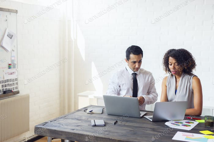 Man and woman using laptops in office