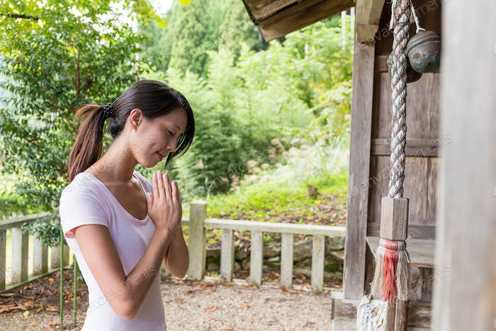 Woman wishing in Japanese temple