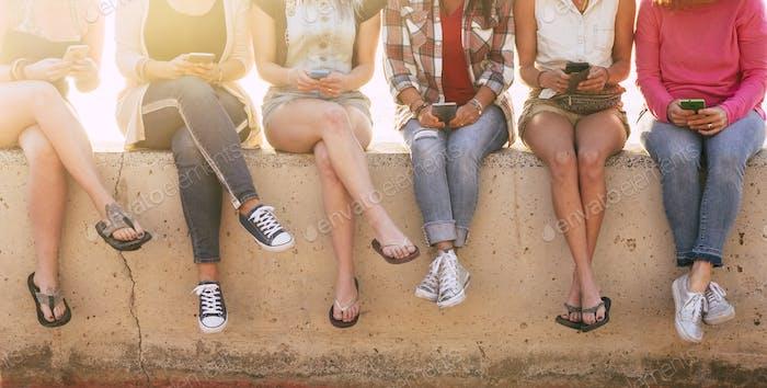 Grupo de chicas irreconocibles con el teléfono