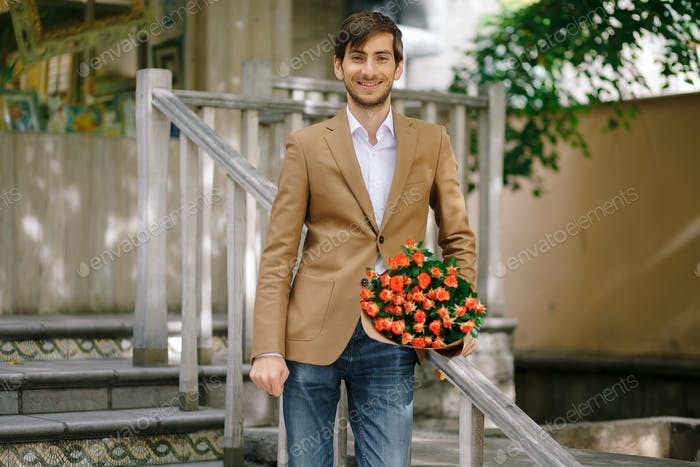 Handsome man holding bouquet of roses talking happy on phone