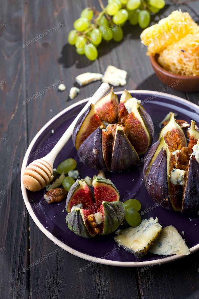Gourmet appetizer of figs with goat cheese,walnuts and honey on ceramic plate