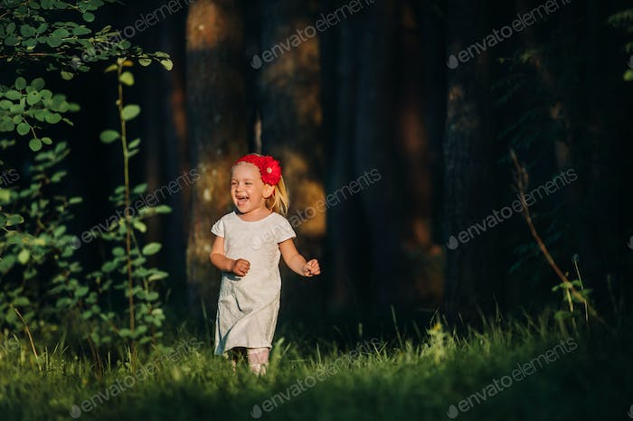 Portrait of a cute little girl runs on a green lawn in a forest. A happy child laughs and smiles