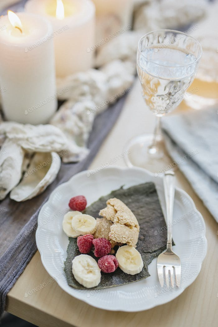 A table for a celebration meal with wine glasses filled and plates of fruit, and lit candles in the