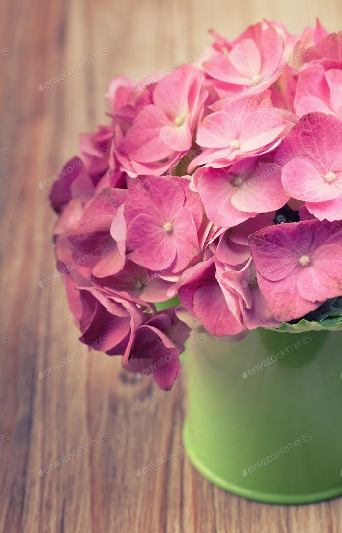Eine hellrosa Hortensienblüte in einer grünen Gießkanne auf einem Vinta