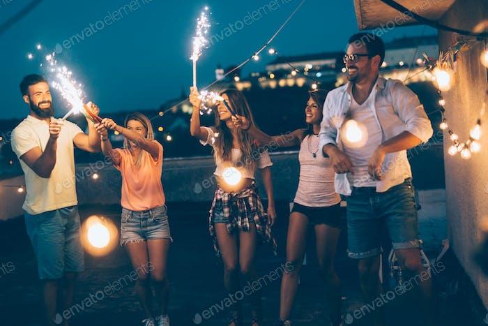 Gruppe von glücklichen Freunden feiern auf dem Dach