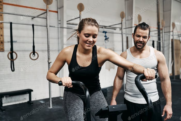 Young woman riding a stationary bike with her gym partner