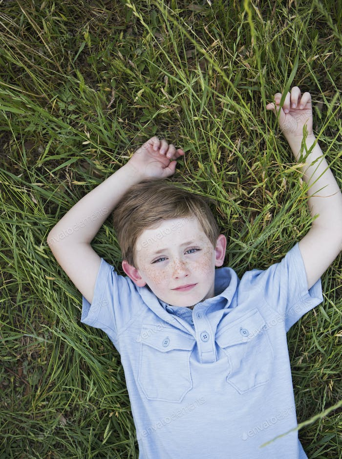 A boy in a blue shirt lying on his back on grass.