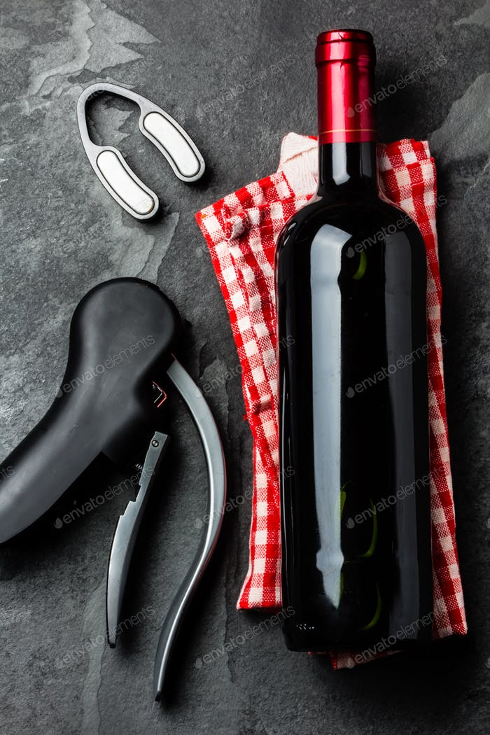Bottle of red wine with corksrew on slate background. Top view