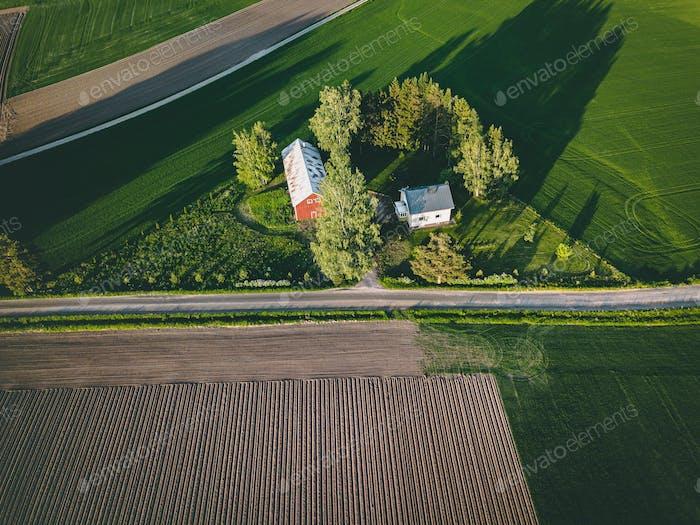 Luftaufnahme von Ackerland mit roten Scheunen und Häusern und Erntefeld in Finnland