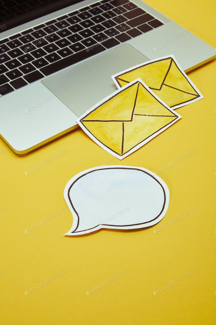Nachrichtenzeichen, Sprechblase und Laptop auf gelber Oberfläche