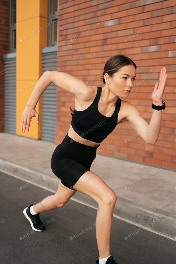 Female fitness model training outside in the city