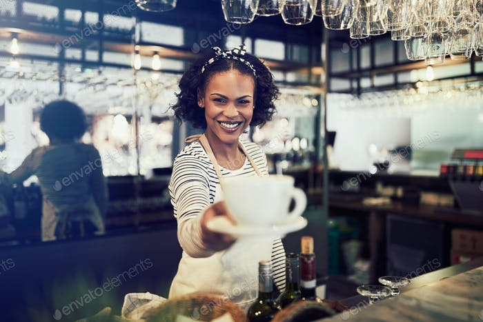Smiling barista holding up a fresh cup of coffee