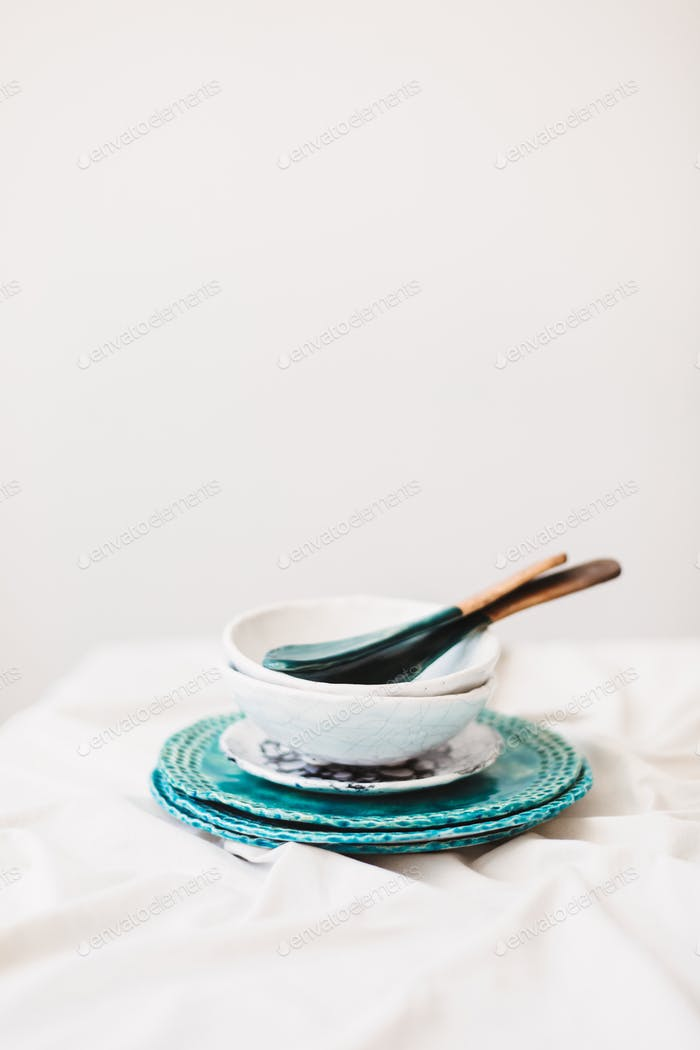 Close up photo of handmade colorful plates,bowl and spoons at pottery studio isolated
