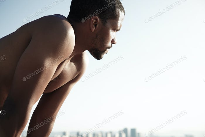 Handsome African American sportsman looking at the sun. Young man put off his clothes exhausted by s