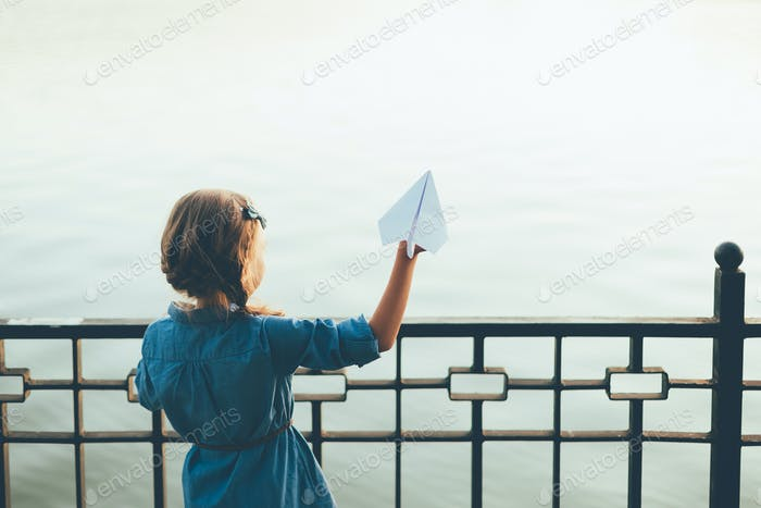 Girl launching toy paper airplane looking to lake