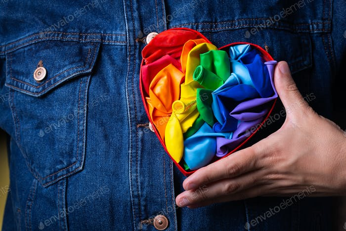 Male hands with heart shaped rainbow lgbtq flag, pride month